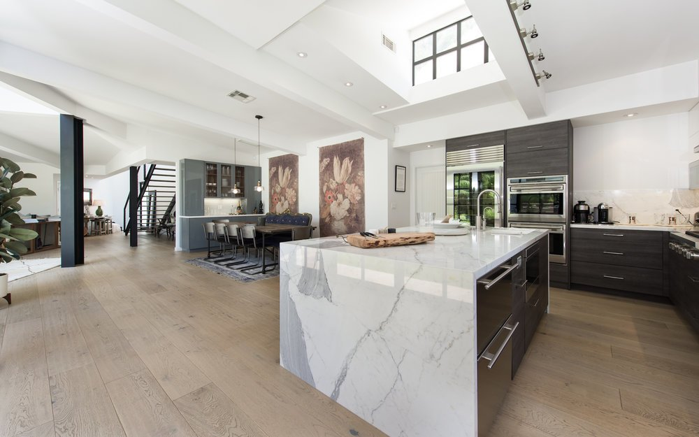 an-open-layout-connects-the-main-living-spacesincluding-a-large-dining-area-off-the-kitchen-skylights-and-walls-of-windows-usher-in-ample-natural-light
