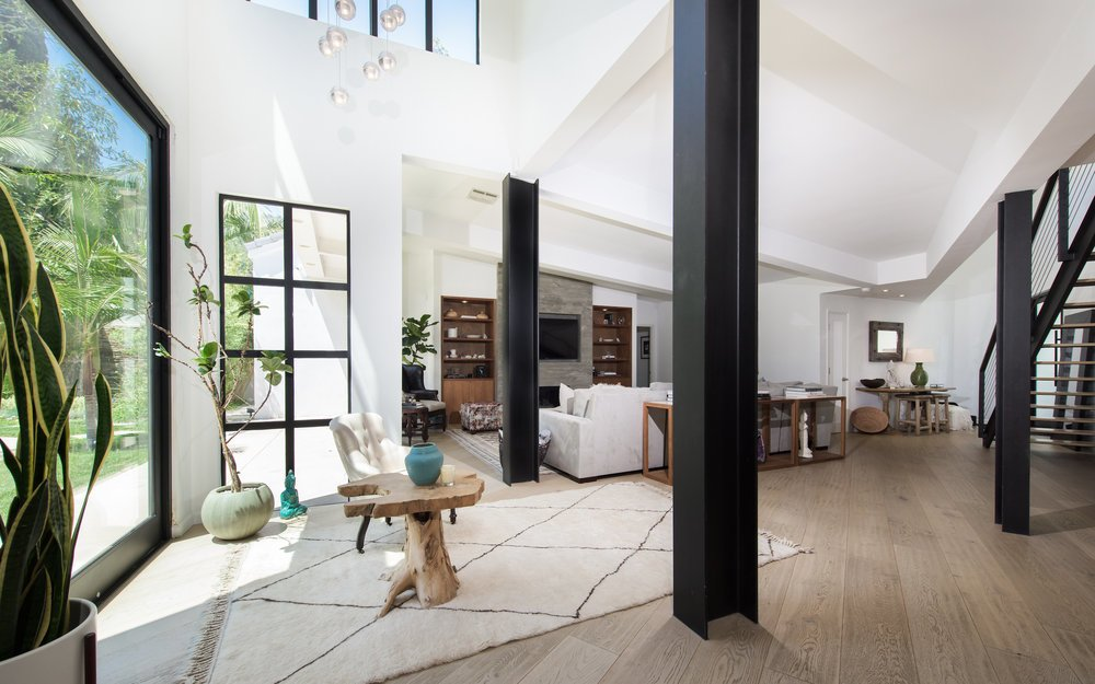 the-airy-living-roomtucked-underneath-a-vaulted-ceilingflows-between-the-kitchen-and-dining-areas-a-staircase-leads-to-a-voluminous-double-height-gym