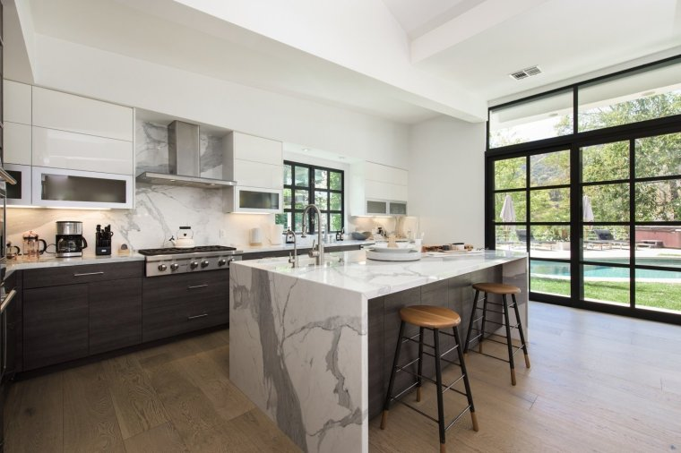 the-remodeled-kitchen-features-high-end-appliances-and-a-marble-wrapped-island